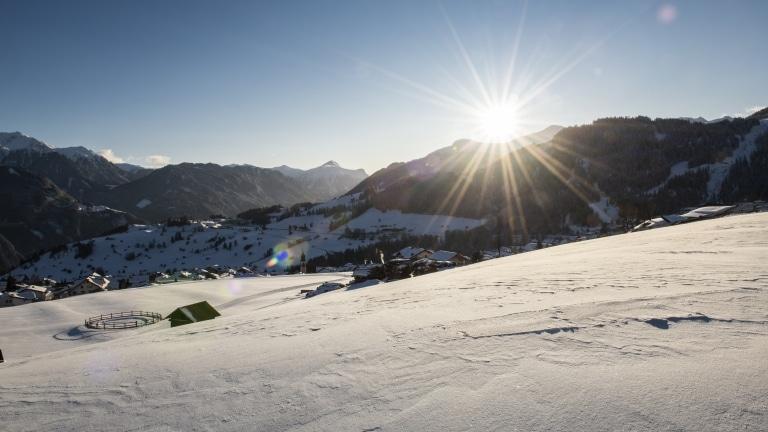 Verschneite Landschaft bei aufgehender Sonne