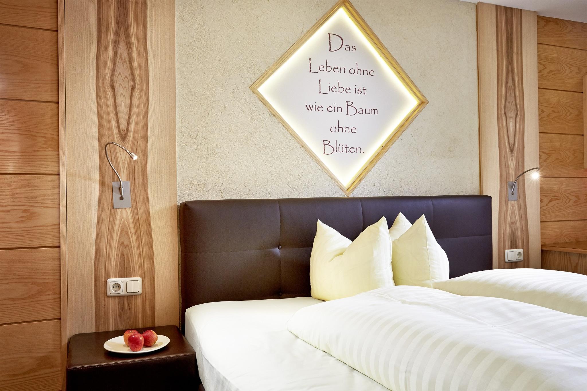 Doppelbett mit Wandspruch