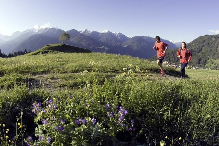 2 Leute joggen über Wiese