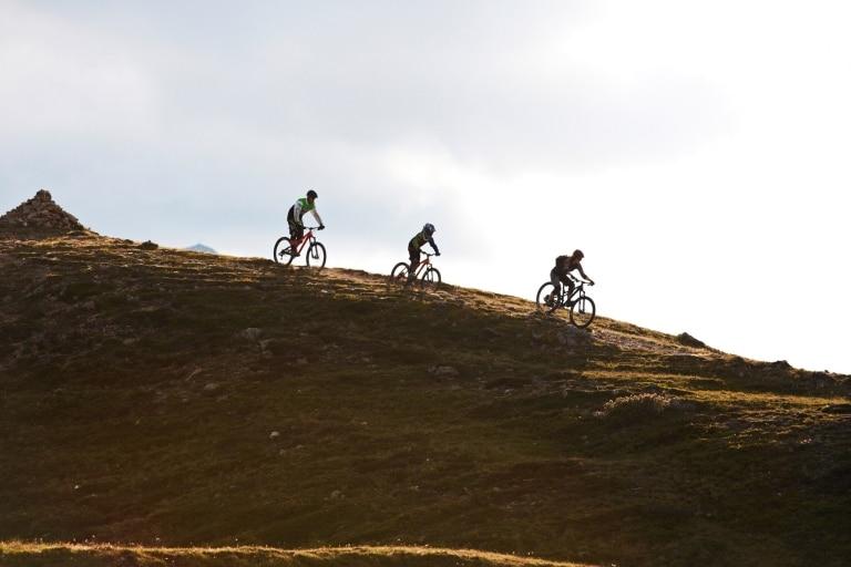 Drei Mountainbiker fahren den Berg hinunter