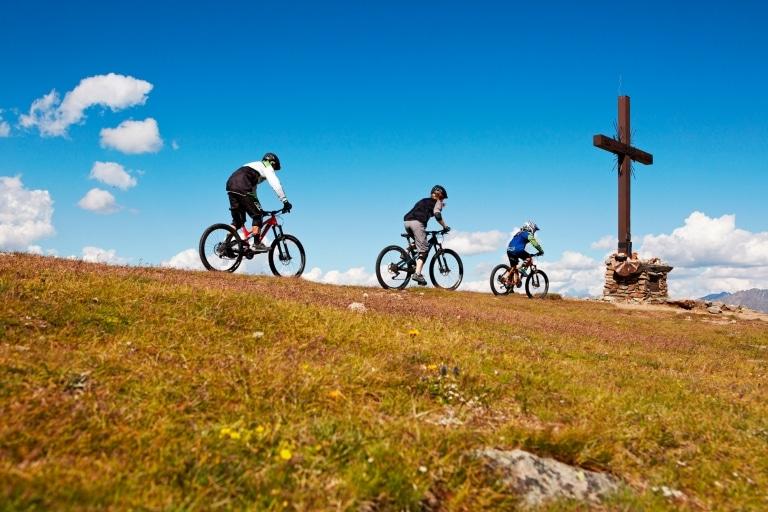 Drei Mountainbiker fahren auf das Gipfelkreuz zu